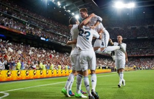 Real Madrid's Gonzalo Higuain from Argentina, left, celebrates with team mates after scoring a goal during a Spanish Supercup, second leg soccer match against FC Barcelona at the Santiago Bernabeu stadium in Madrid, Wednesday, Aug. 29, 2012. (AP Photo/Daniel Ochoa de Olza)